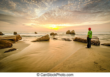 Man standing near the beach looking at sun rising