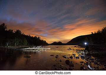 Man standing near the edge of the water at Jordan Pond