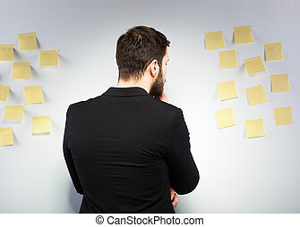 Man standing next to a wall with postits - businessman...