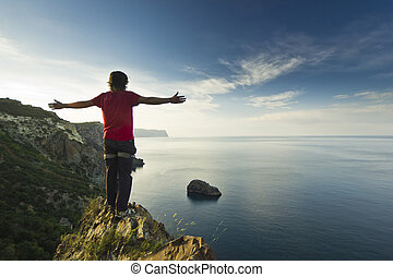 man standing on a cliff in mountains with hands up