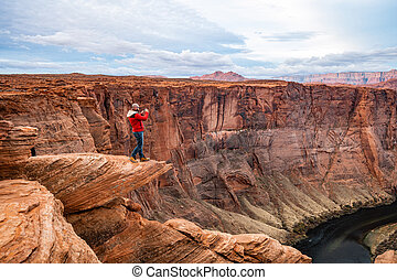 Man standing on a cliff over Colorado river at Horseshoe bend viewpoint at Glen Canyon, Arizona, USA.