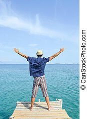 Man standing on a dock at seaside