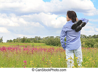 man standing on a meadow with sneakers in his hands