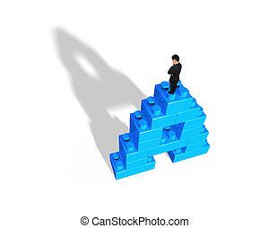 Man standing on alphabet letter A shape stack blocks