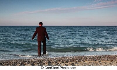 Man standing on beach, then going and immersed to sea water...