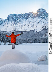 Man standing on frozen lake spreading hands to mountain...