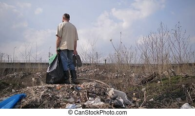 Man standing on garbage hill at landfill site - Mature...