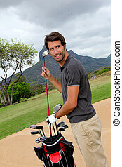 Man standing on golf course with equipment