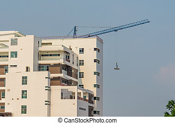 man standing on iron bars held up by mega crane.