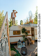 Man standing on rv roof, trailer camping