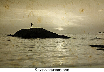 Man standing on small stone during sunset.
