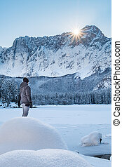 Man standing on snow covert lake looking to mountain...