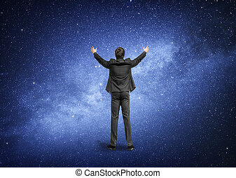 Man standing on the background of the night sky, the Milky Way galaxy.