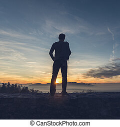 Man standing on the edge of a stone wall looking in to the distance