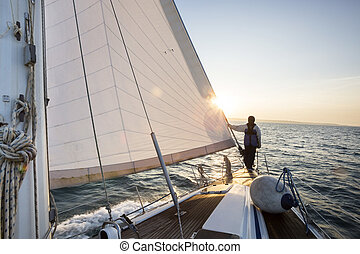 Man Standing On The Front Of Sail Boat In Sea