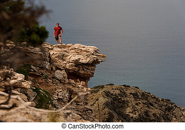 Man standing on the rock near the sea water