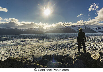 man standing on the stone above Grey glacier in patagonia at sunset