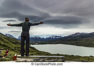 man standing on the stone above lake in patagonia with grey sky