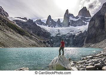 man standing on the stone above lake near fitz roy mountain, patagonia