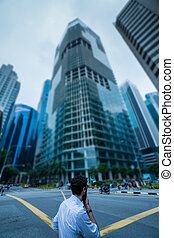 Man standing on the street against modern skycrapers - Back ...
