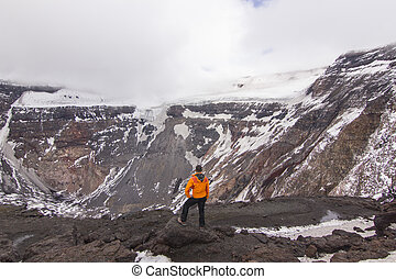 man standing on Tolbachik volcano crater with snow on hills