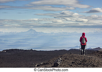 man standing on volcanic slag with view on snowy volcanoes