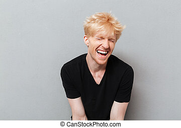 Man standing over grey wall near copyspace laughing.