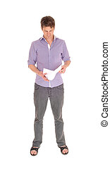 Man standing reading some papers.