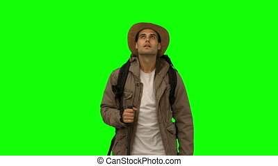 Man standing under leaves falling on green screen in slow...