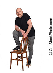 man standing with a chair in white background