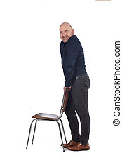 man standing with a chair in white background, side view