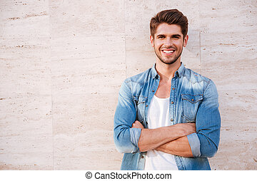 Man standing with arms crossed - Cheerful young man standing...