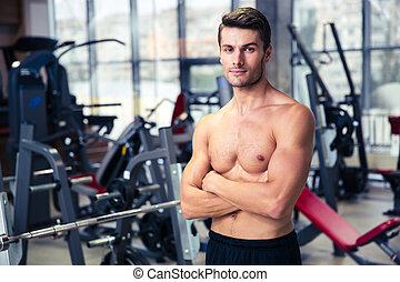 Man standing with arms folded at gym