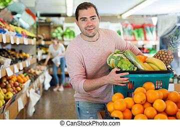 Man standing with full grocery cart during shopping in fruit shop