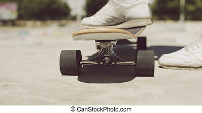 Man standing with one foot on a skateboard