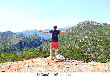 man standing with open hands in front of the mountains at ...