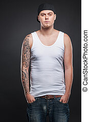 man standing with tattoo on hand and looking. young cool guy holding hands in pockets