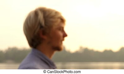Man Stands And Puts His Hair in Order at the Riverbank at Sunset in Slo-Mo