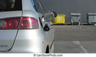 Man stands at the gas station and fueled his silver car