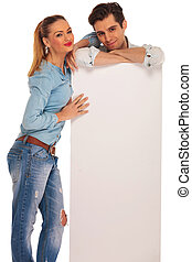 man stands behind billboard while woman rests