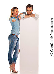 man stands behind blank billboard with woman