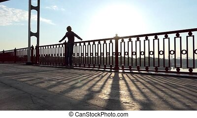 Man Stands, Breathes Deeply, Raises Hands, at Sunset on a...