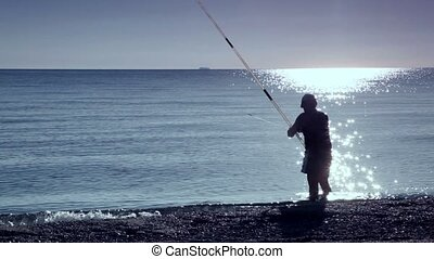 Man stands in sea water and fishing