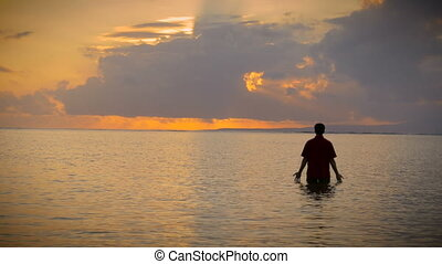 Man stands in the ocean with rays of light coming in and his...