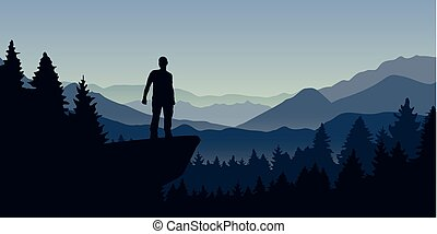 man stands on a cliff in the forest with mountain view nature landscape