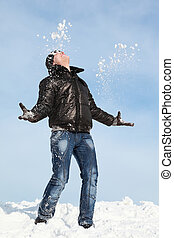 Man stands on snow throwing him  hands and looks in sky