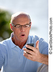 Man staring at his mobile phone is disbelief