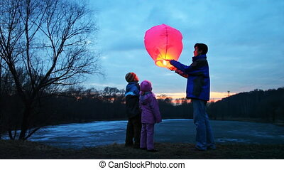 man starts chinese lantern of  forest, its son and daughter look at it, part4