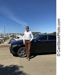 Man staying near luxury black car parked near yachts marine