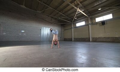 Man staying on his hands and moving his legs - Showing...